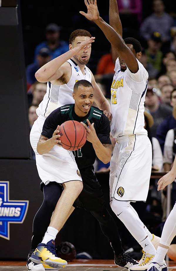 Hawaii guard Quincy Smith gets pressured by Cal center Kameron Rooks, left, and Roger Moute a Bidias.