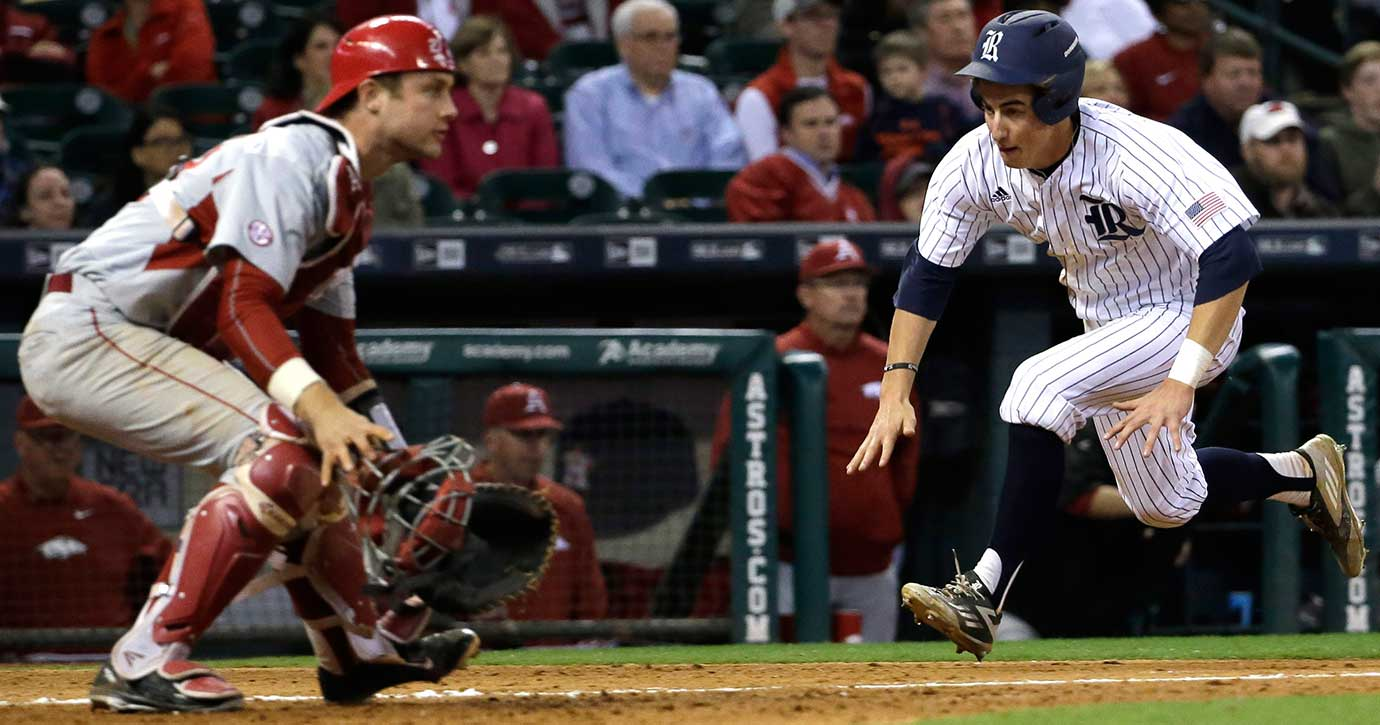 Rice's Ford Proctor  runs toward home plate to score a run as Arkansas catcher Tucker Pennell waits for the throw.