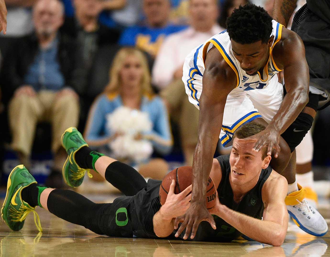 Oregon guard Casey Benson tries to keep the ball from UCLA guard Isaac Hamilton.
