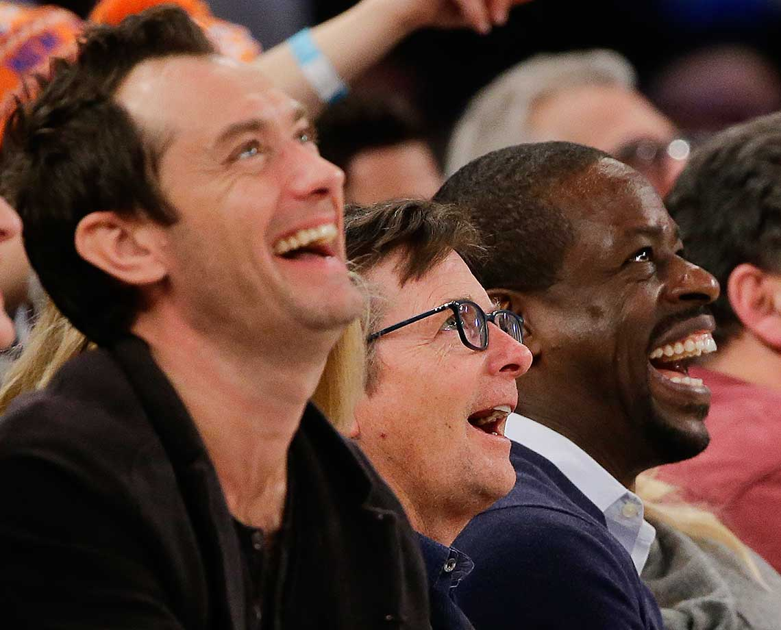 Flanked by actors Jude Law and Courtney Vance, right, Michael J. Fox reacts to images on the big screen at MSG.