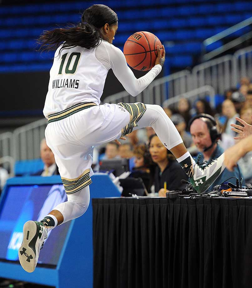 South Florida's Courtney Williams leaps onto a courtside table while chasing the ball during a first-round women's college basketball game against Colorado State in the NCAA Tournament.
