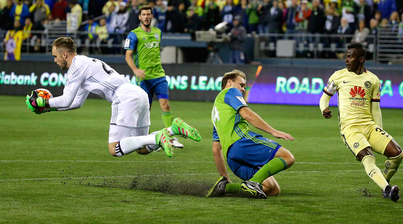 Seattle's Stefan Frei comes out of the box to grab the ball, next to Club America's Darwin Quintero and Sounders defender Chad Marshall.