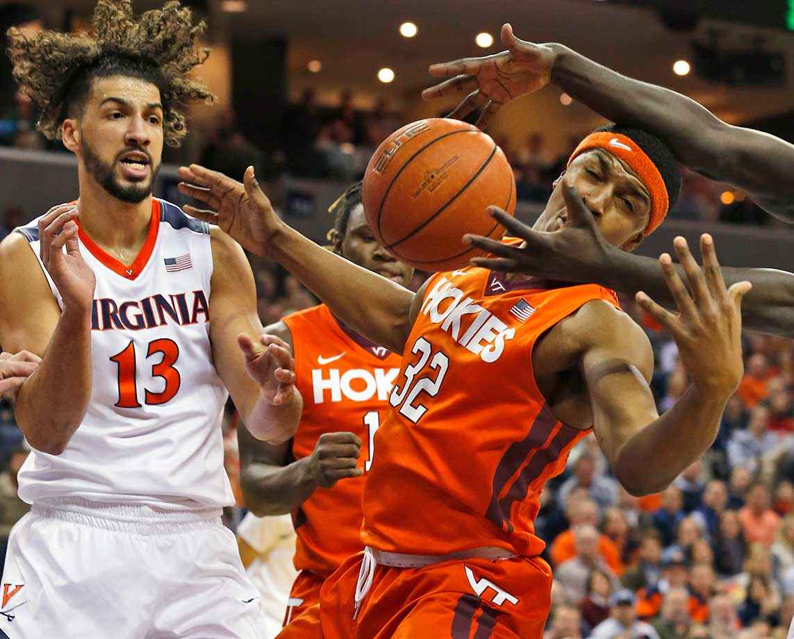 Virginia's Anthony Gill and Virginia Tech's Zach LeDay reach for a rebound in Charlottesville, Va.