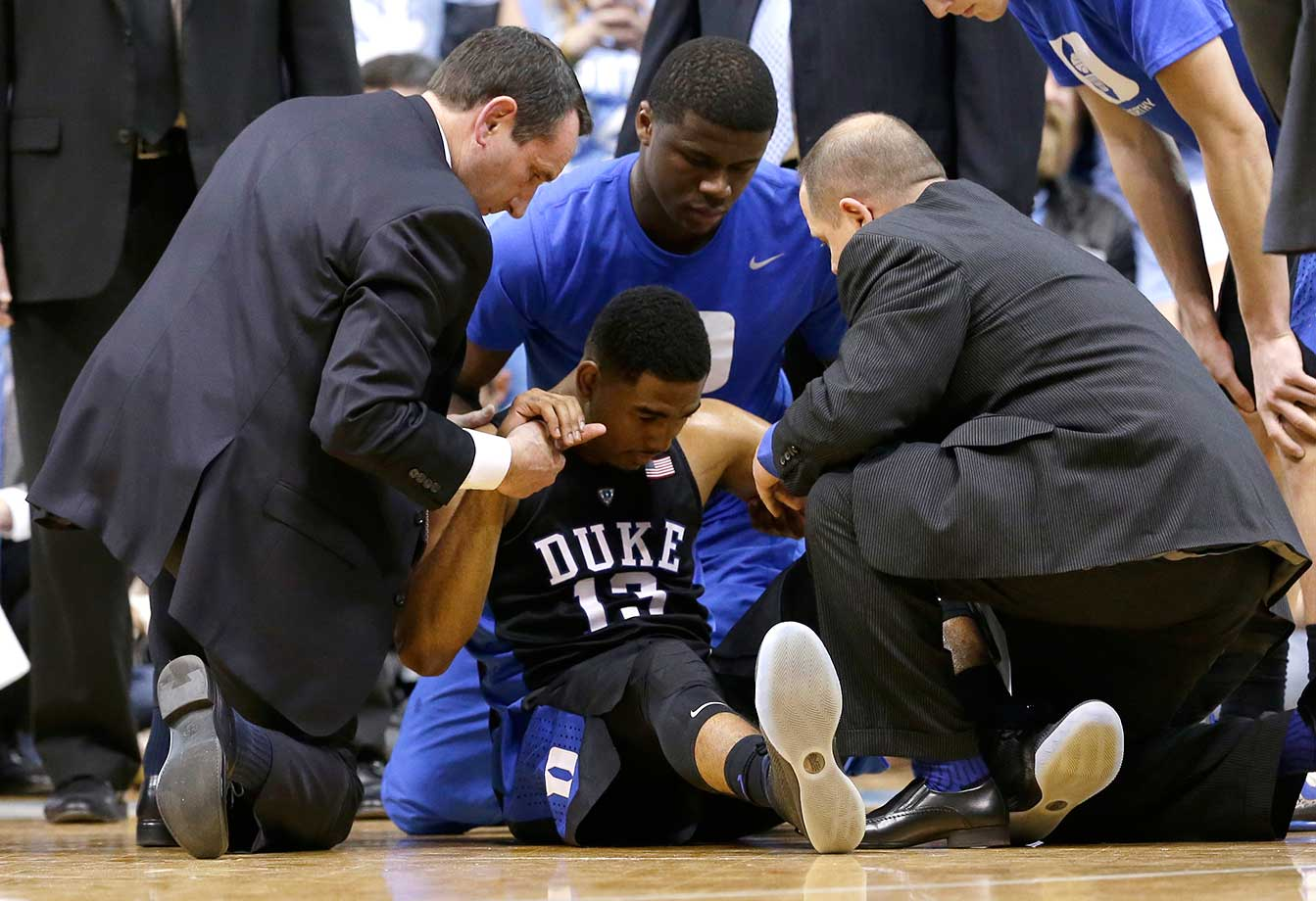 Duke head coach Mike Krzyzewski helps an injured Matt Jones, who sprained his ankle early against North Carolina.