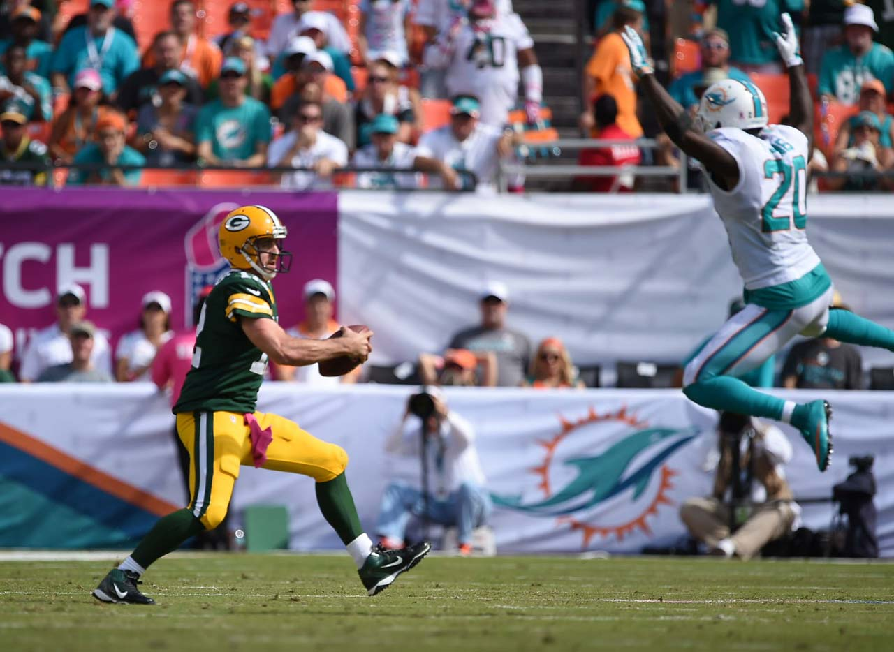 Aaron Rodgers attempts to complete a play while being pressured by Reshad Jones of Miami.