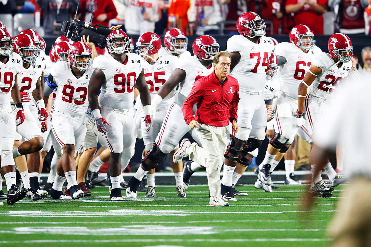 Nick Saban leads his players onto the field.