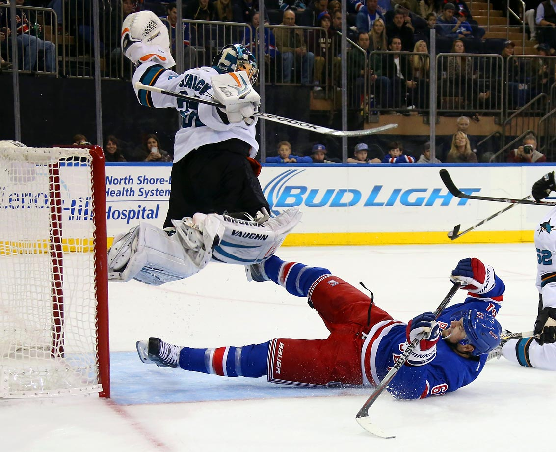 The Sharks' goalie jumps to avoid a sliding Nash during the Sharks-Rangers game at Madison Square Garden on Oct. 19.