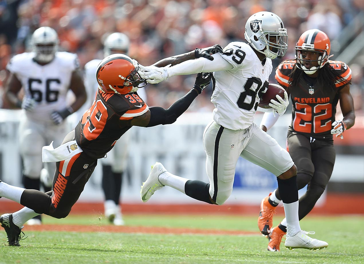 Amari Cooper stiff arms Tashaun Gipson of the Cleveland Browns.