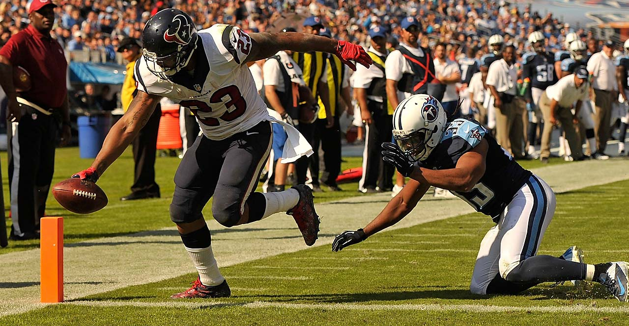 Arian Foster of the Houston Texans scores a touchdown around Michael Griffin of the Tennessee Titans.