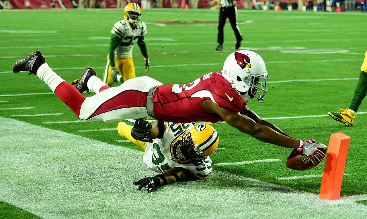 John Brown dives for the pylon while being hit by defensive end Datone Jones.