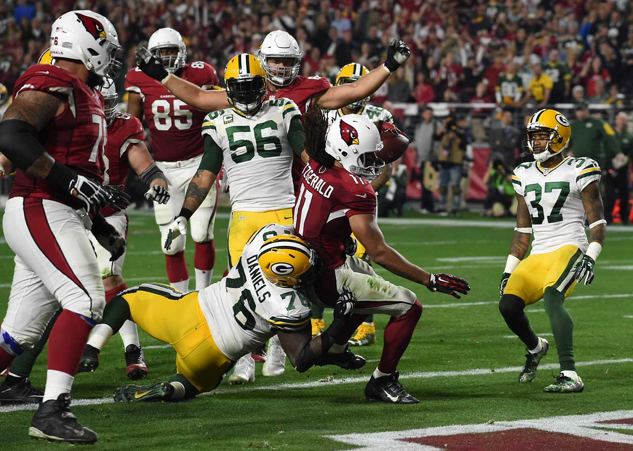 Scenes from Arizona's 26-20 overtime victory against Green Bay in the divisional round of the NFL playoffs, which ended on a shovel pass touchdown from Carson Palmer to Larry Fitzgerald.