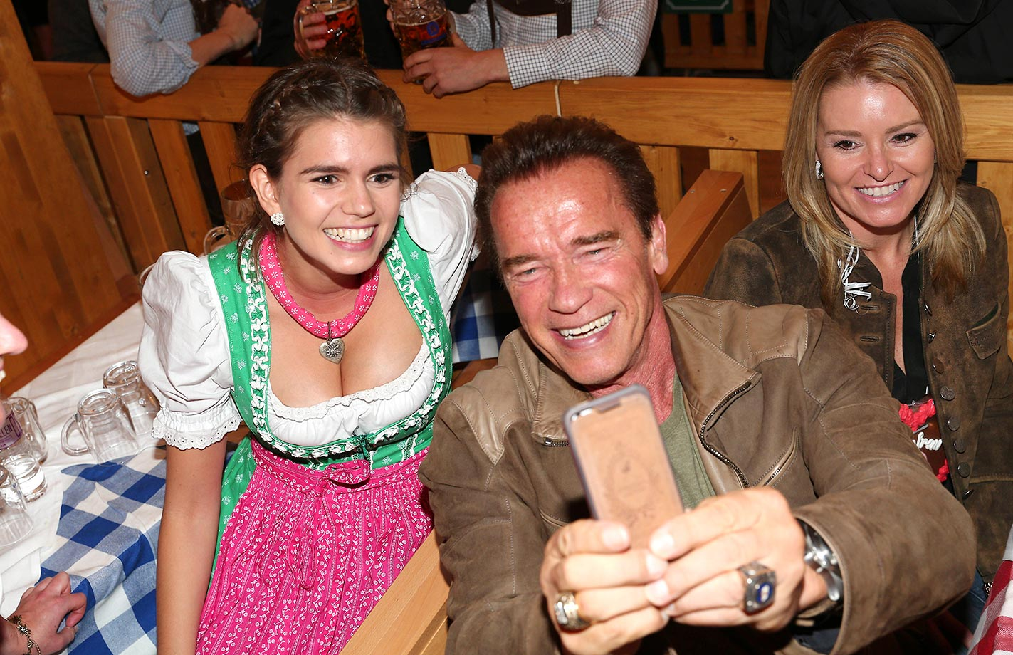 Arnold Schwarzenegger and Heather Milligan (right) visit the Schuetzenfestzelt during Oktoberfest 2015.
