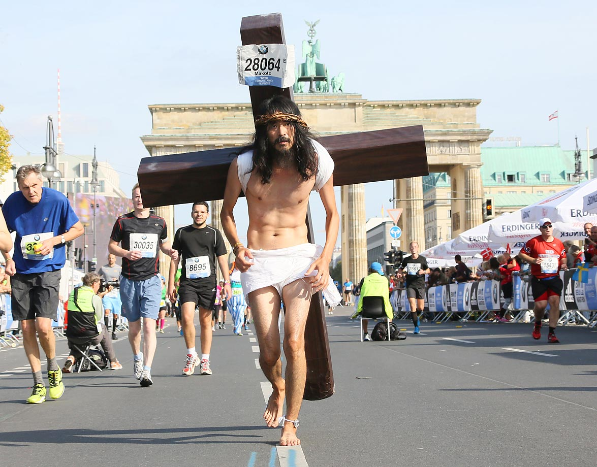A participant dressed as Jesus runs in front of Brandenburger Gate during the 41th edition of the Berlin Marathon.
