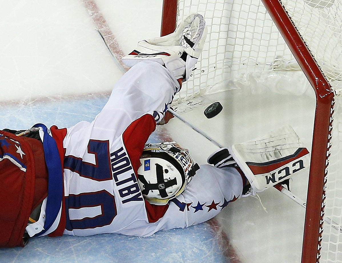 The puck gets past Washington Capitals goalie Braden Holtby for the winning goal in overtime of Game 7 of the Eastern Conference semifinals. The Rangers won 2-1.