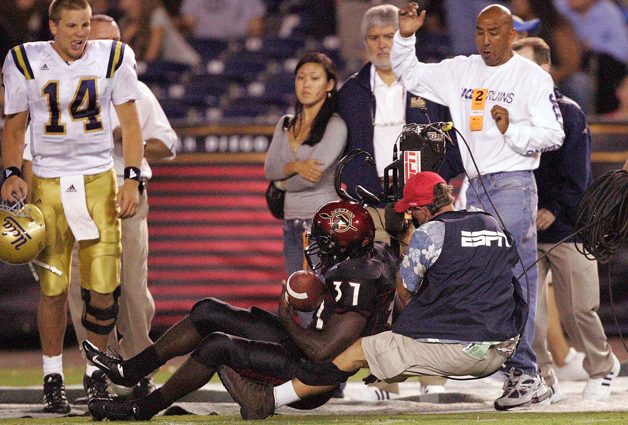 Brandon Bornes of San Diego State takes out an ESPN cameraman on the sidelines during a 2005 game against UCLA at Qualcom Stadium.