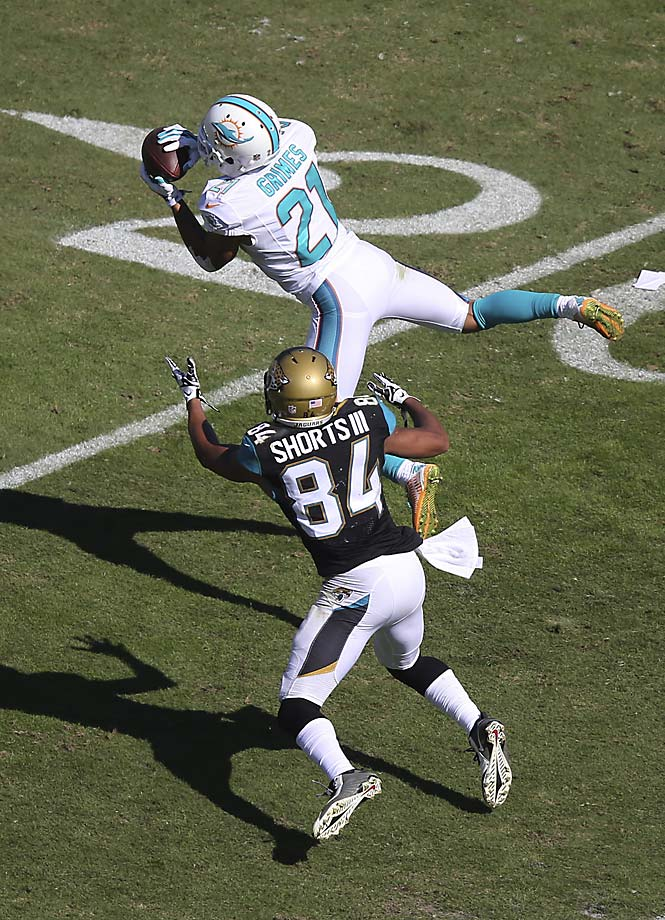 Miami Dolphins cornerback Brent Grimes intercepts a pass in front of Jacksonville Jaguars wide receiver Cecil Shorts.