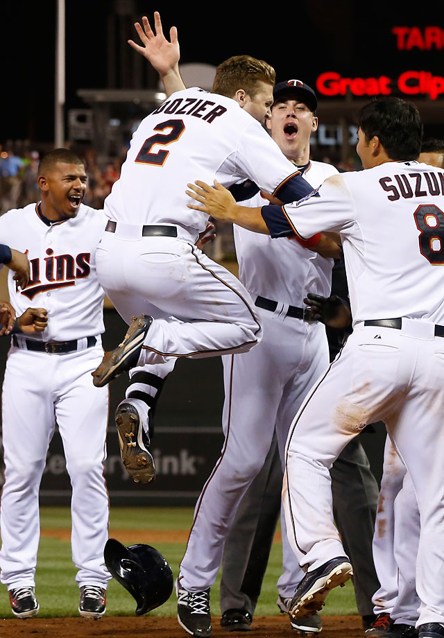 Brian Dozier leaps into the air as teammates wait to congratulate him on a walk-off, three-run home run in the ninth inning that gave Minnesota an 8-6 victory over Detroit on July 10. The Twins scored seven runs in the ninth inning to erase a 6-1 deficit.