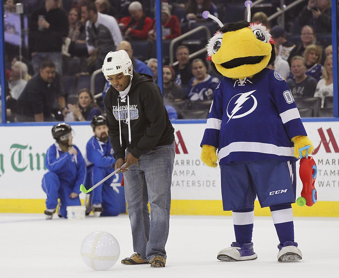 A Lightning fan takes part in a little game of on-ice golf with his caddy Thunderbug, the Tampa Bay Lightning mascot.