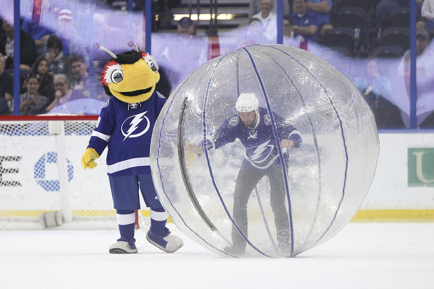 Thunder Bug, the Tampa Bay Lightning mascot, helps out a fan who is participating in a human hamster race during a game against the Nashville Predators.