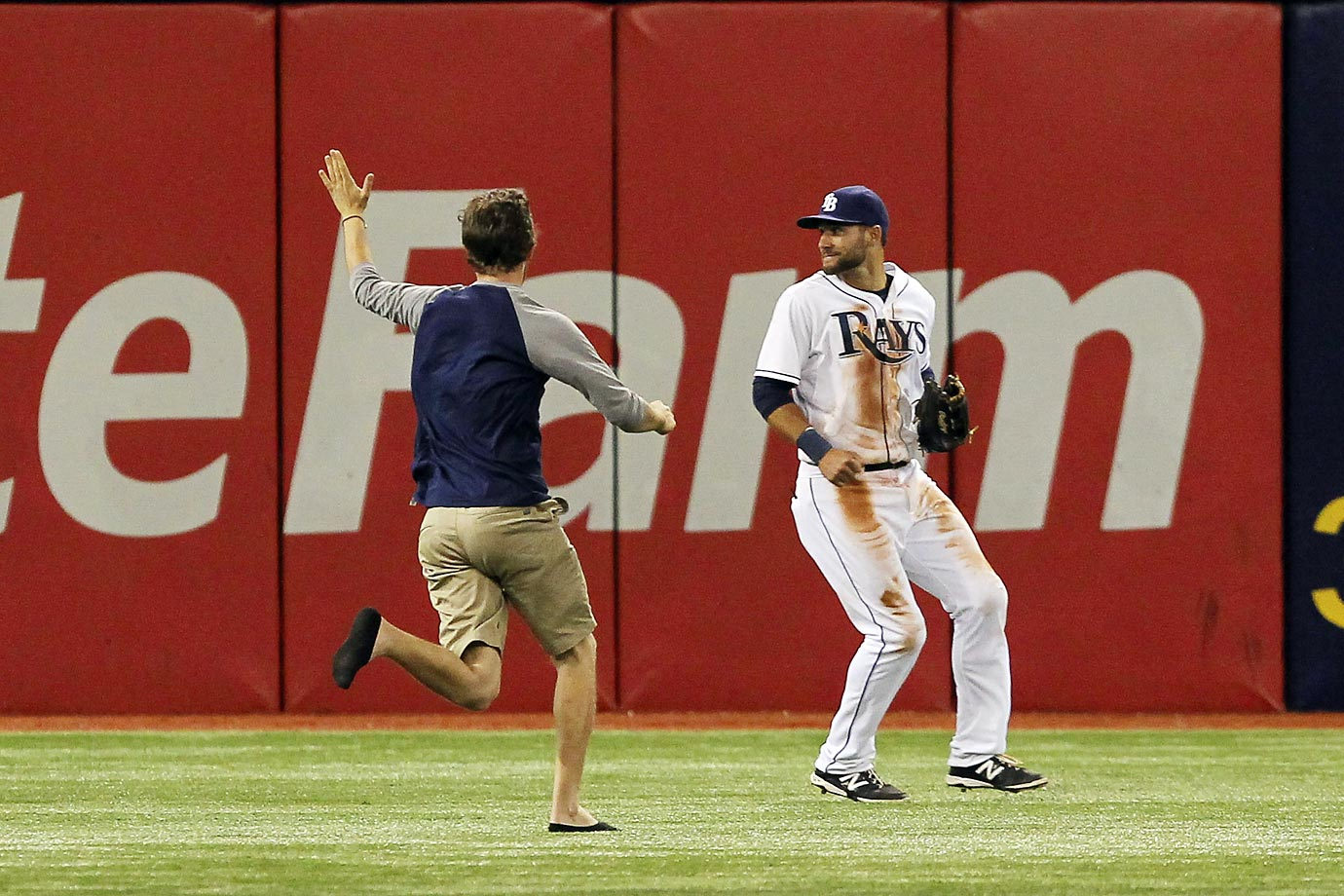 Kevin Kiermaier of the Rays does his best to avoid a Florida fan who ran on to the field in the 9th inning of their game against the Orioles.