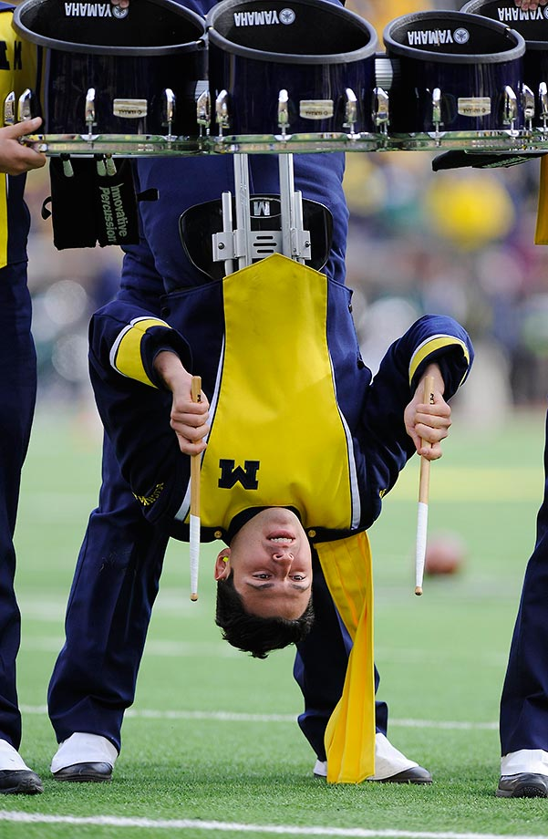 A member of the Michigan Marching Band drum line plays upside down while performing at UM's game against Michigan State.