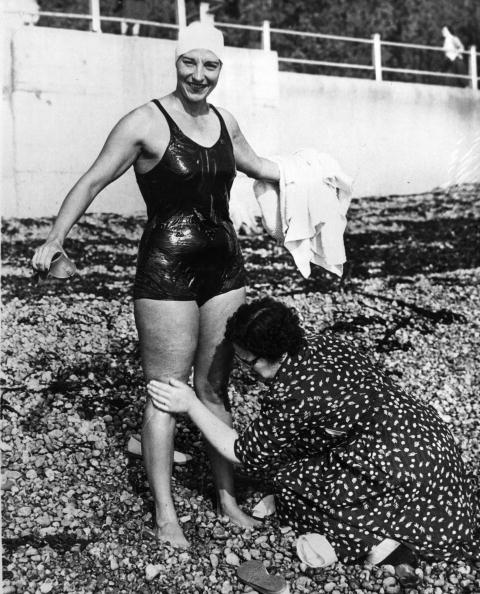11th October 1955: Miss Florence Chadwick (1917 - 1995), a swimmer from San Diego in California, is being given a rub-down before entering the water at St Margaret's Bay near Dover, Kent for her attempt at a non-stop double crossing of the English channel. She first swam both ways from France to England in 1950 and from England to France in 1951 and 1955.