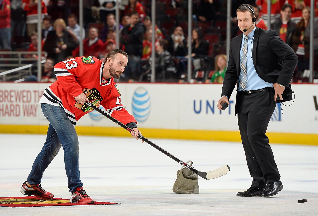 Former WWE wrestler CM Punk shoots the puck in between periods of the game between the Los Angeles Kings and the Chicago Blackhawks.