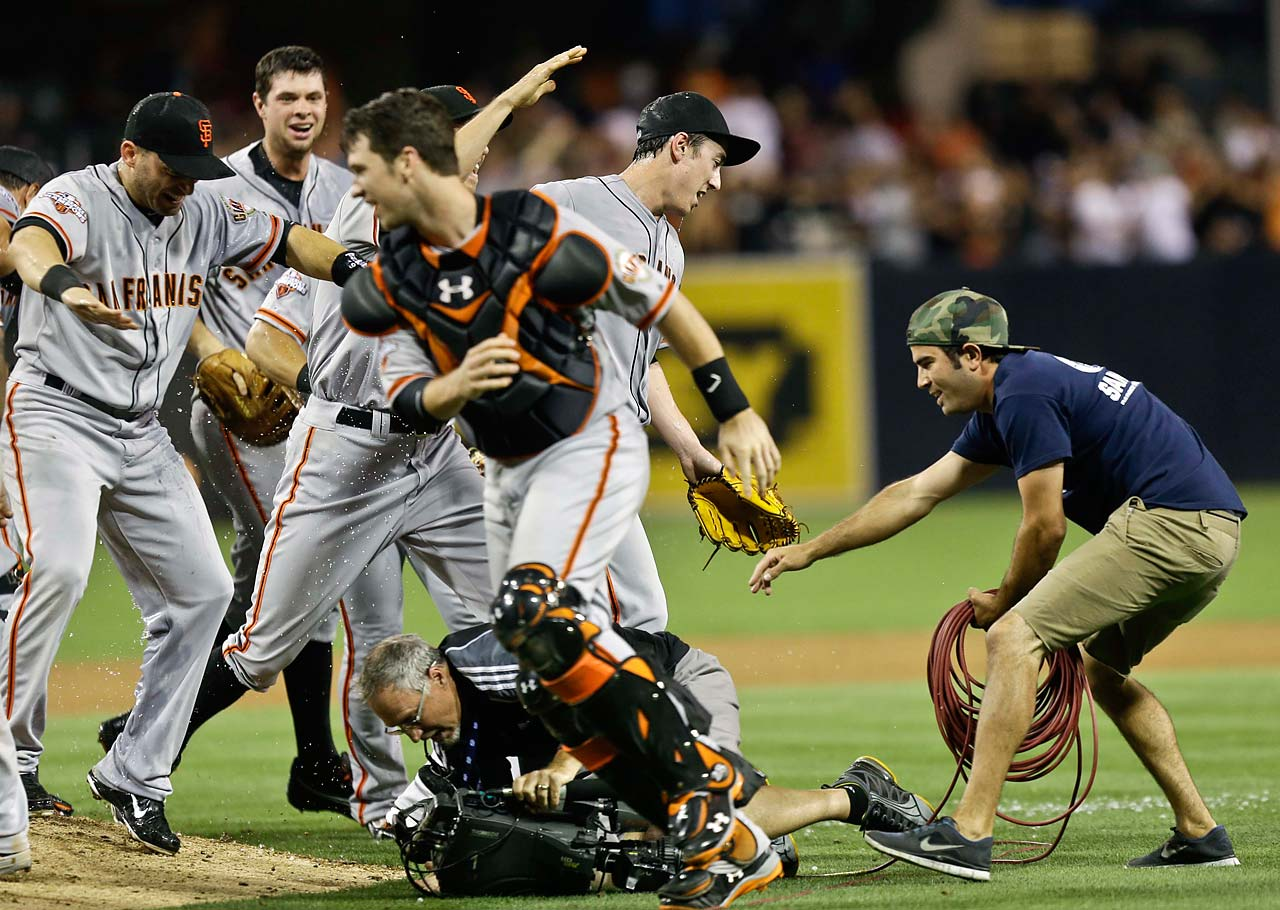 San Francisco Giants starting pitcher Tim Lincecum, right, steps out of the pile of players celebrating his July 2013 no hitter against the San Diego Padres as a television cameraman hits the ground in San Diego.