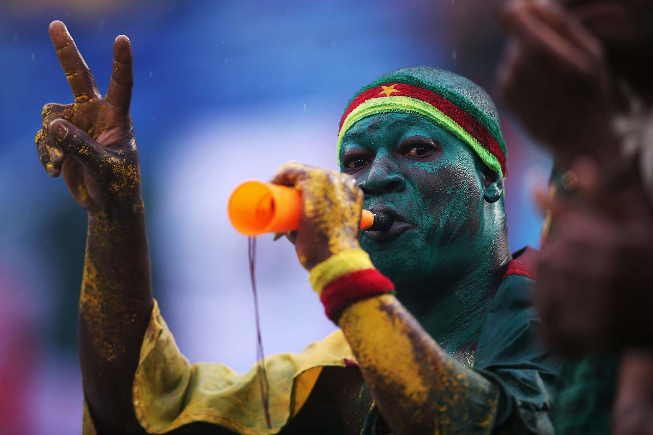 A Cameroon fan blows a horn in the rain during the match between Mexico and Cameroon.