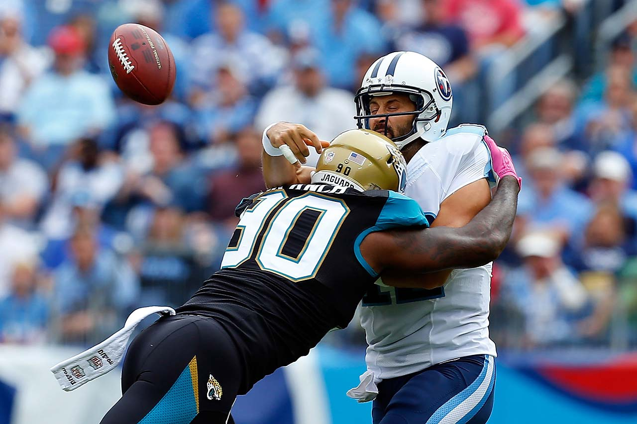 Charlie Whitehurst of the Tennessee Titans is hit by Andre Branch of the Jacksonville Jaguars.