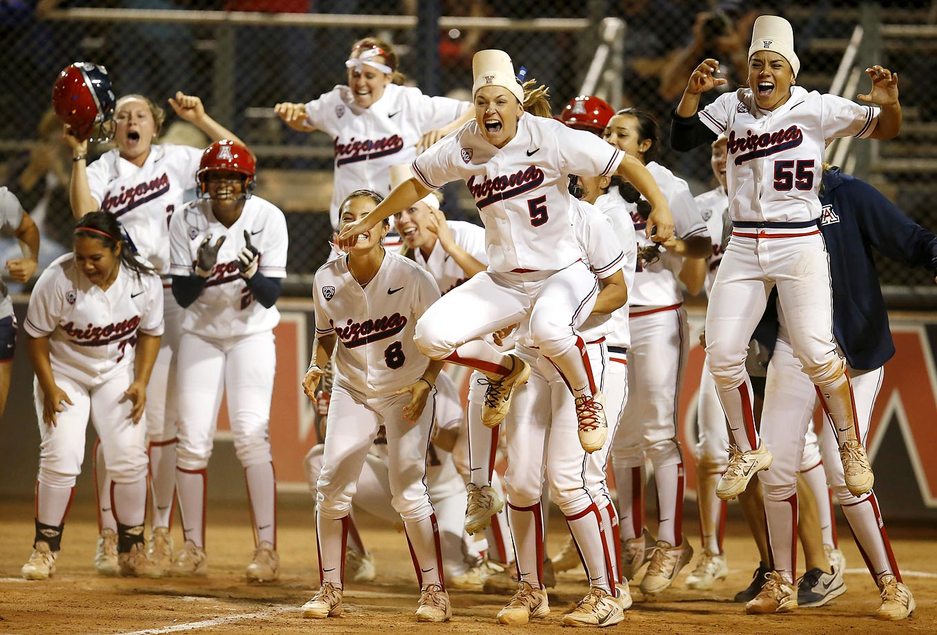 Arizona celebrates after Chelsea Goodacre tied the game with a two-run home run against Minnesota during an NCAA college softball tournament regional championship game.