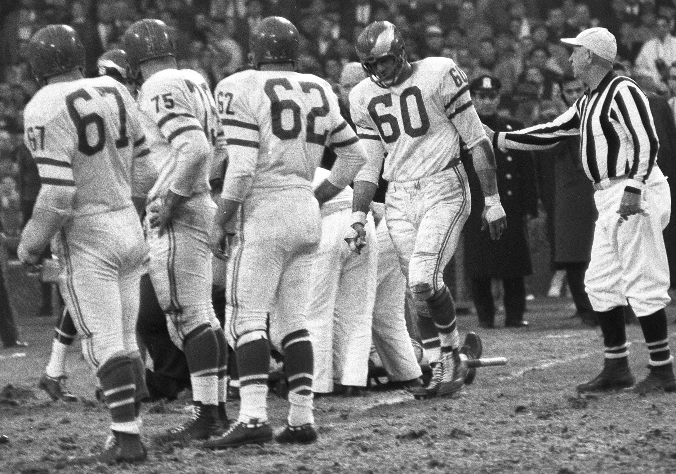 A referee talks with Chuck Bednarik his tackle on Frank Gifford at Yankee Stadium. Gifford (background) was knocked out and, because of this injury, did not play for 18 months.
