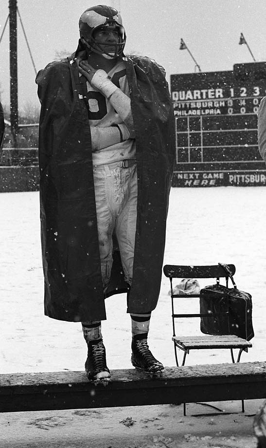 Chuck Bednarik standing on the sidelines bench during a game vs. the Pittsburgh Steelers at Forbes Field.