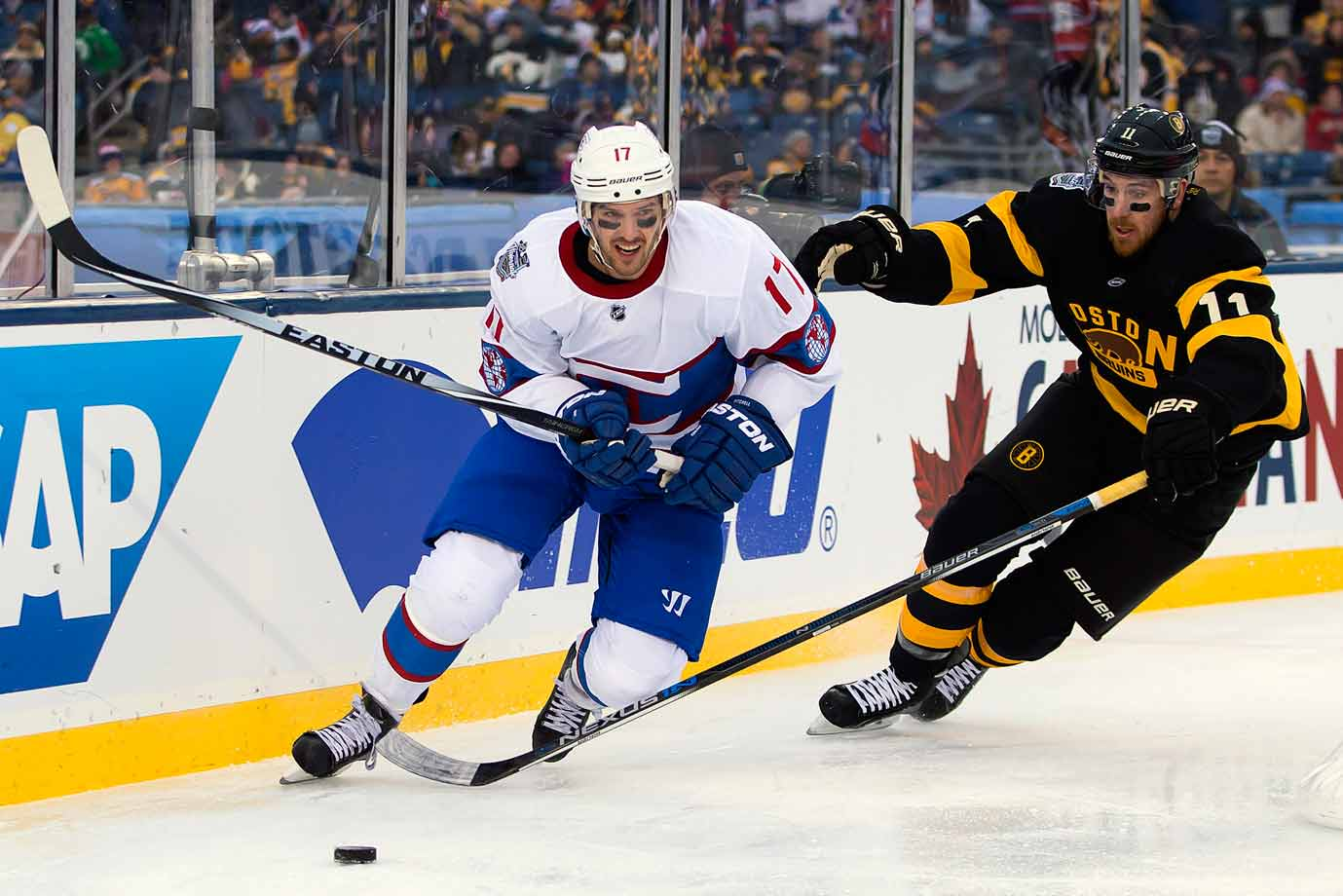 Montreal's Torrey Mitchell and Boston's Torey Krug pursue the puck.