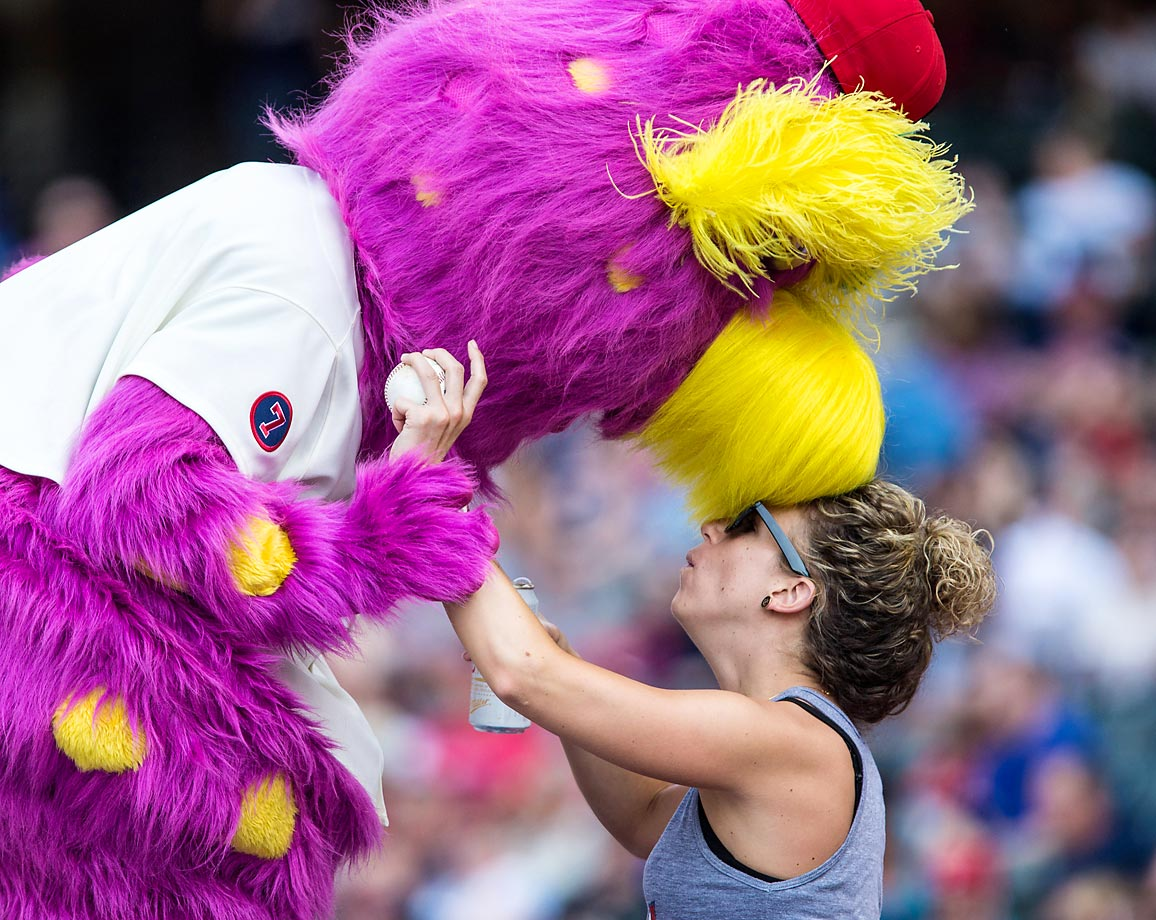 Slider, the Cleveland Indians mascot, plants a kiss on a fan during a game against the Minnesota Twins.