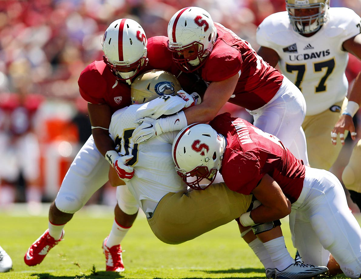 Colton Silveria of UC Davis is tackled by Kevin Anderson and Blake Martinez during a 45-0 loss to Stanford on Aug. 30.