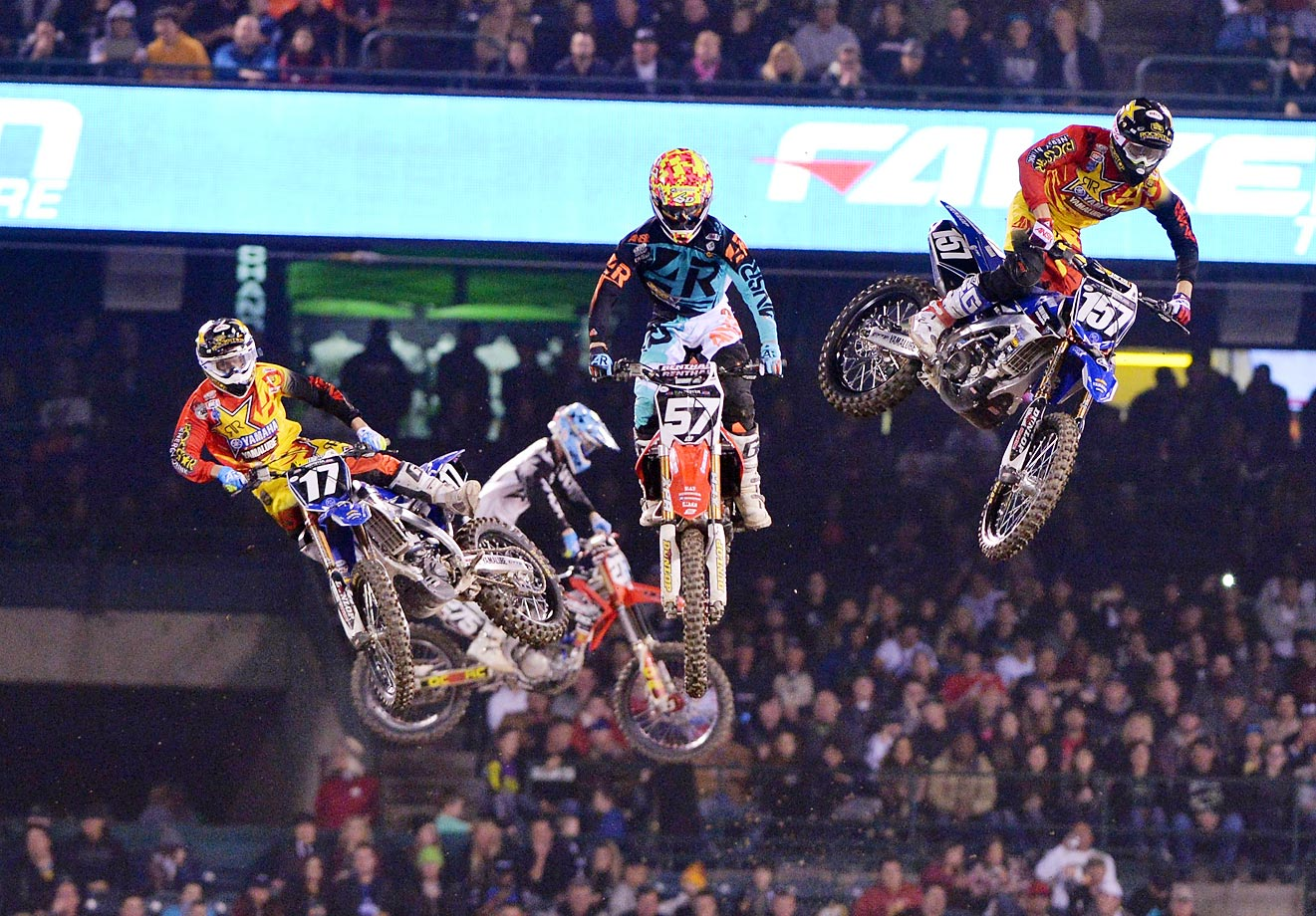 Cooper Webb (17) and teammate Aaron Plessinger (157) battle around midpack at the Monster Energy/AMA Supercross at Angel Stadium in Anaheim.