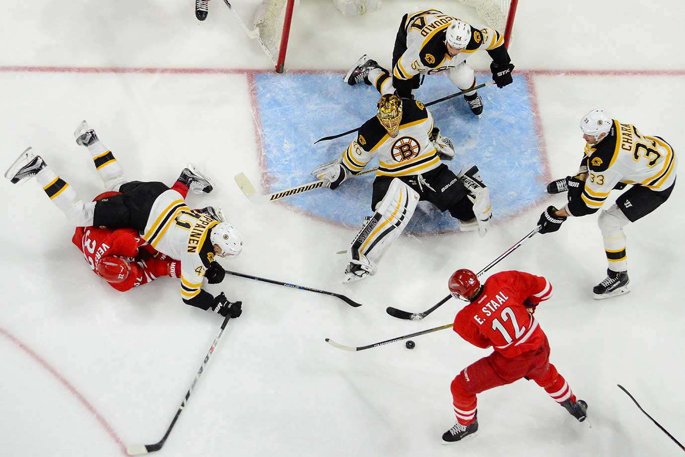 Boston goalie Tuukka Rask defends a shot attempt by Carolina's Kris Versteeg and Eric Staal.