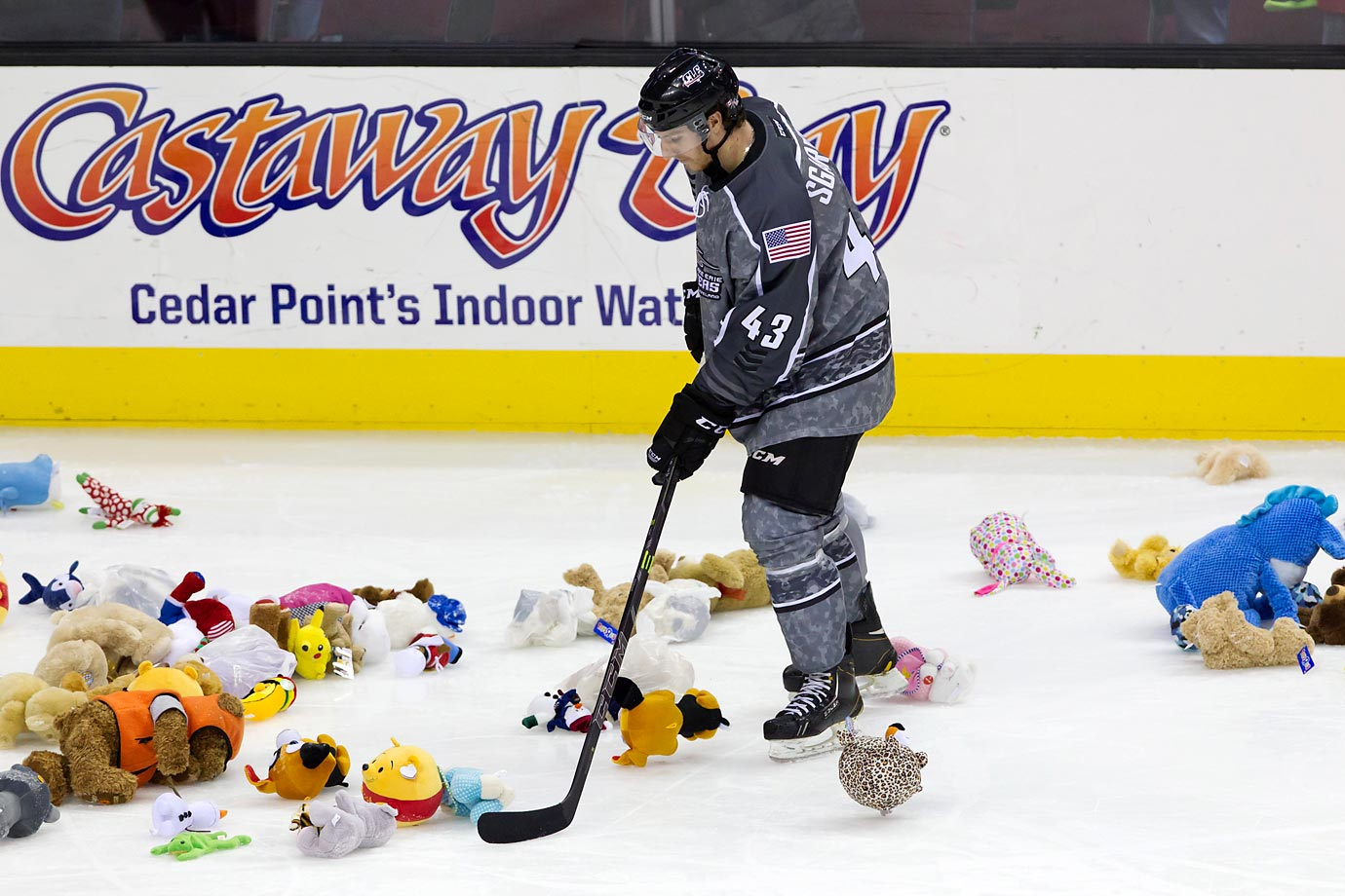 "Mike Sgarbossa of the Lake Erie Monsters helps to collect stuffed animals after the Monsters scored their first goal of the game as part of the annual ""Chuck-a-Bear"" holiday promotion."