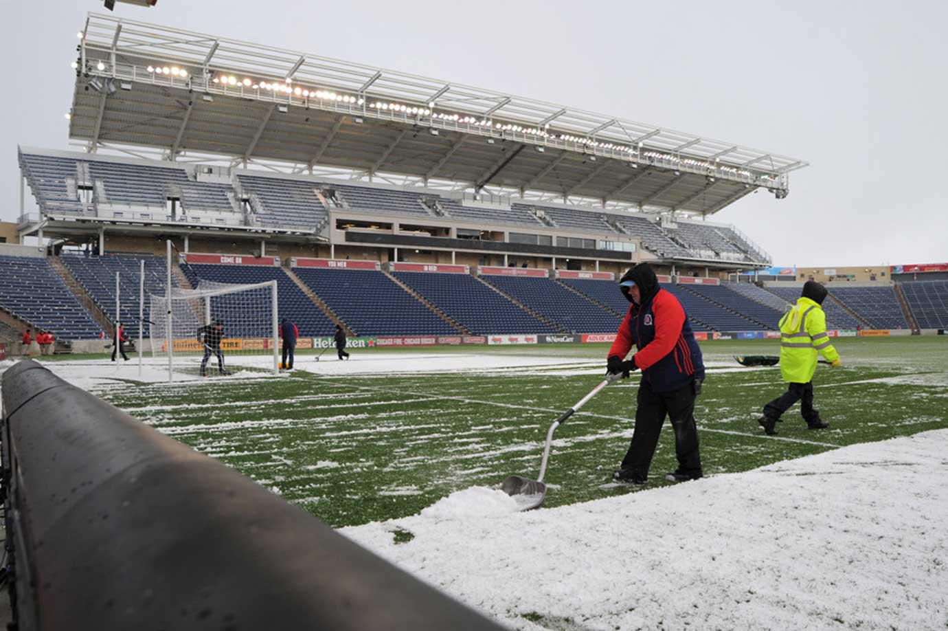 Workers clear the field prior to a game between the Philadelphia Union and Chicago Fire in Bridgeview, Ill.