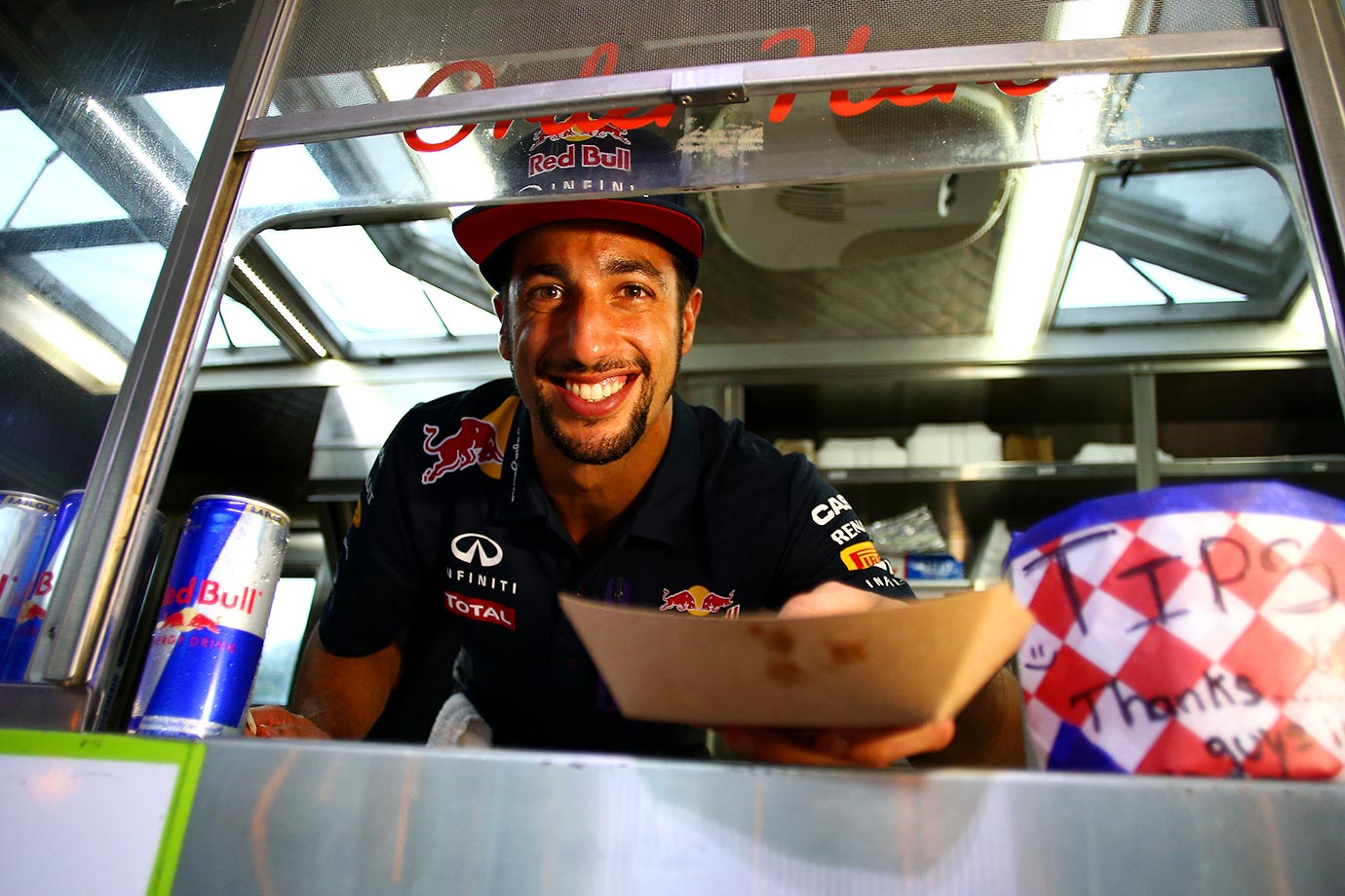 Daniel Ricciardo of Infiniti Red Bull Racing serves at a food truck during previews to the United States Formula One Grand Prix in Texas.
