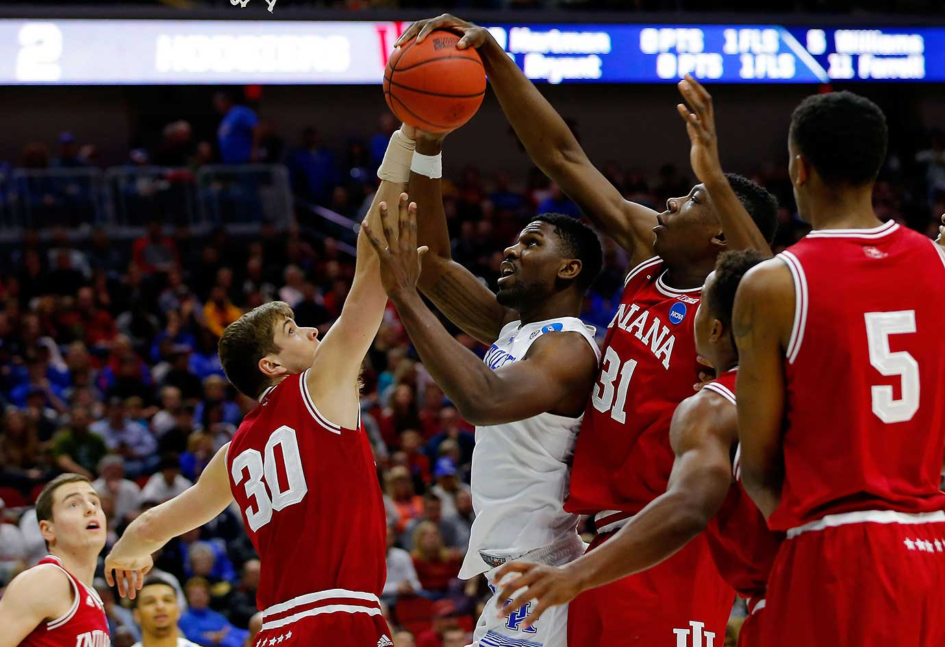Alex Poythress of Kentucky goes up against Thomas Bryant (31) and Collin Hartman (30) of Indiana.
