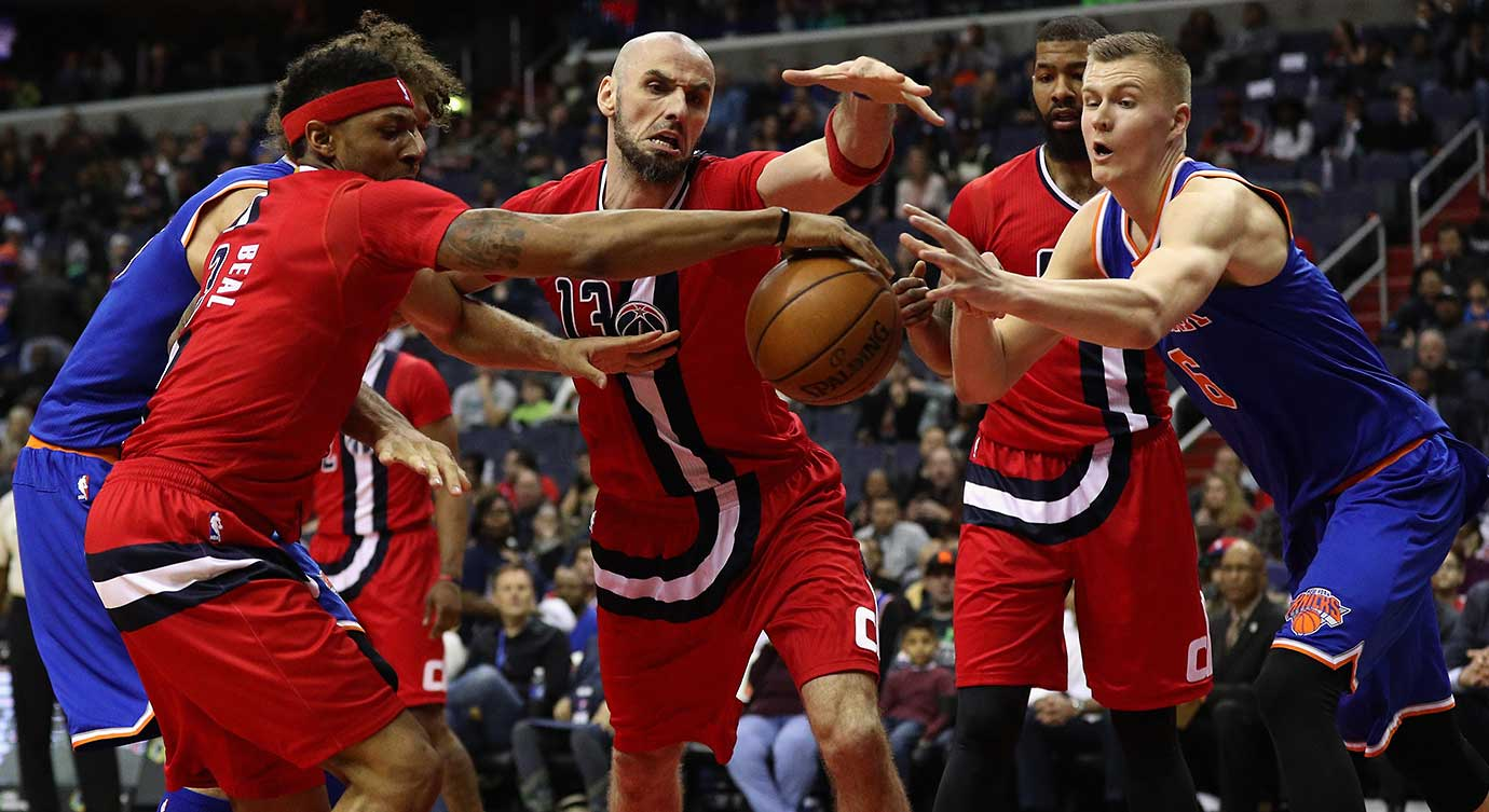 Bradley Beal (3) and Marcin Gortat (13) of Washington try to get a loose ball before Kristaps Porzingis of the Knicks can.