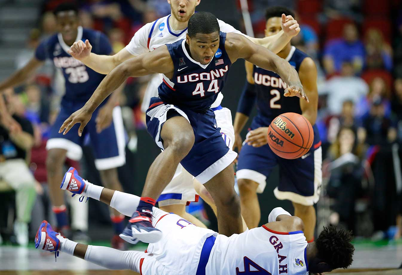 Connecticut guard Rodney Purvis leaps over Kansas guard Devonte' Graham while chasing down a loose ball.