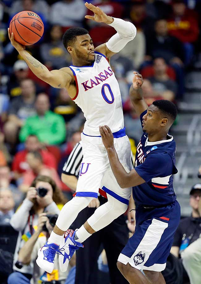 Kansas guard Frank Mason III passes over UConn's Sterling Gibbs as the tournament's No. 1 overall seed advanced to the Sweet 16.