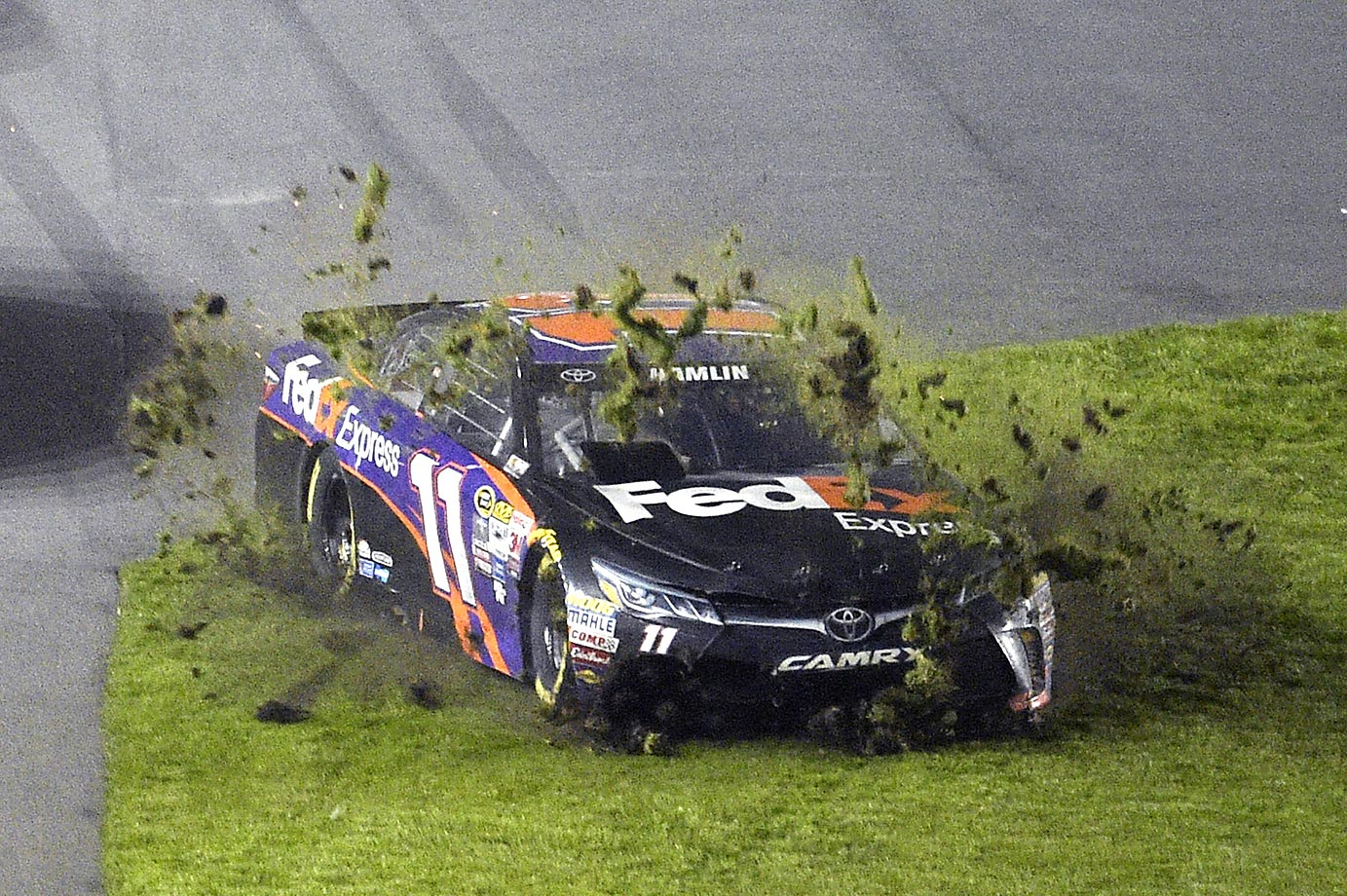 Denny Hamlin digs up the infield grass while trying to avoid a multi-car accident.