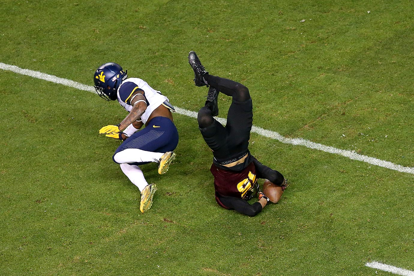 Devin Lucien of ASU is upended by Ricky Rumph of West Virginia.