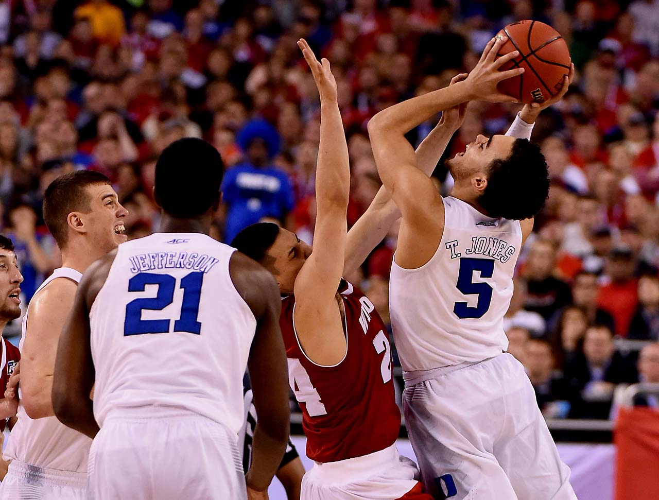 Duke point guard Tyus Jones hoists a tough lay-up over Wisconsin's Bronson Koenig. Jones was the Blue Devils' hero, scoring 23 points and drilling several clutch 3-pointers.