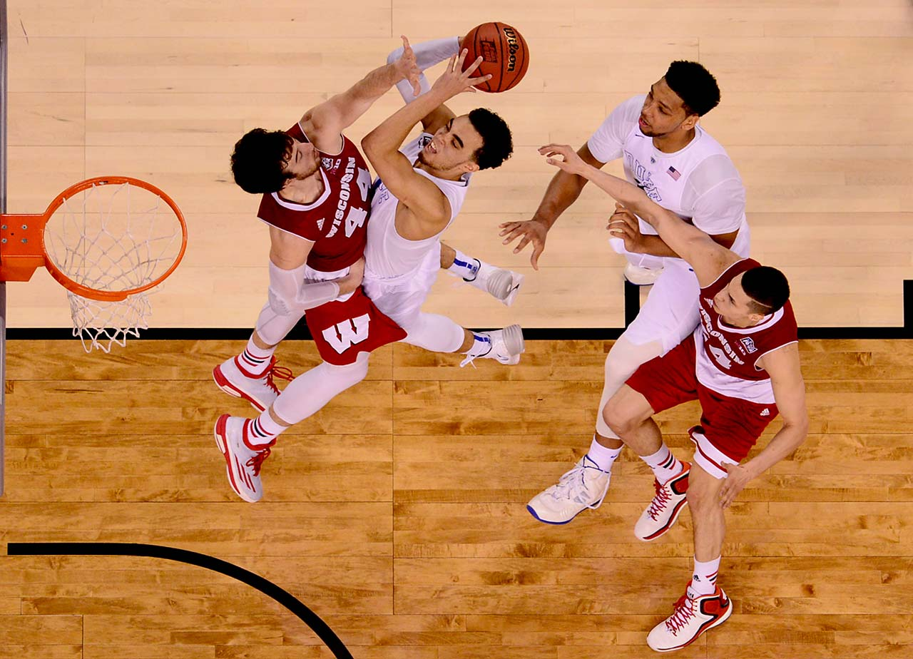 Duke guard Tyus Jones clashes with Wisconsin center Frank Kaminsky as the freshman attempts to score at the basket. Jones (23 points) and Kaminsky (21 points) led their respective teams in scoring Monday night.