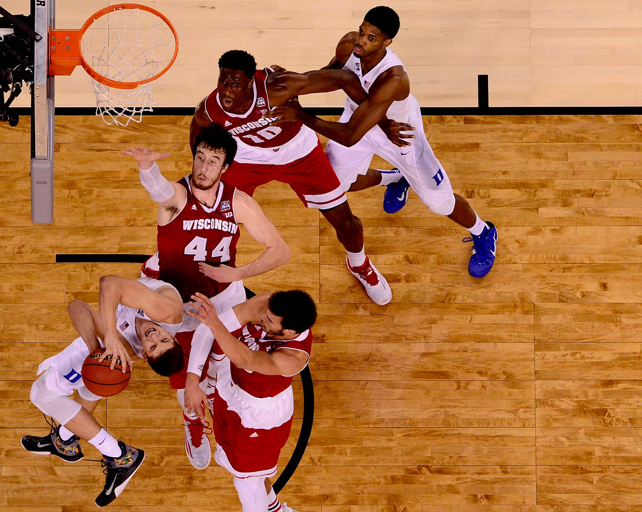 Duke guard Grayson Allen contorts his body to lift a shot over two Wisconsin defenders. In addition to 5-8 shooting, Allen reached the free throw line five times and made all five shots.